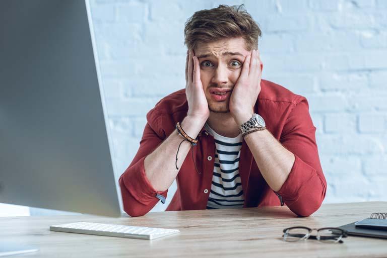 Man looking upset at a computer
